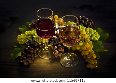 two glasses of wine and grapes on wooden