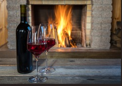 Two glasses of wine and wine bottle near cozy fireplace, in country house, winter vacation.