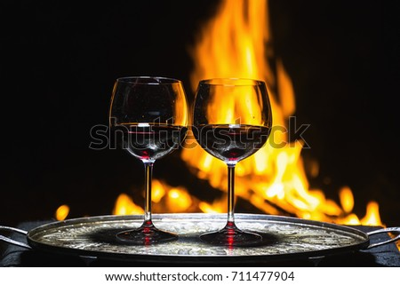 two glasses of wine on the background of fire #711477904