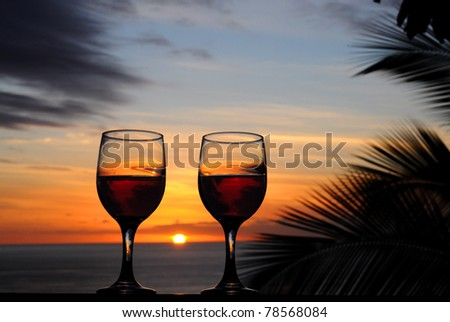 Two glasses of wine reflecting the tropical sunset.