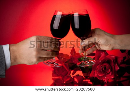 Two glasses of wine, rose and heart on a red background. Valentines day card.