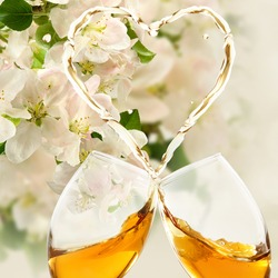 Two glasses of wine that spill out and form a stylized heart.  Romantic banner. Decoration of beautiful flowers