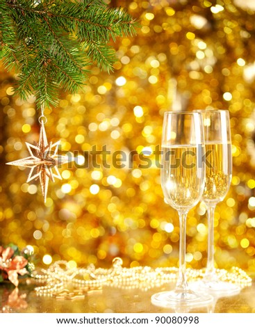 Two glasses of wine with a Christmas decor in the background. very shallow depth of field, focus on near glass.