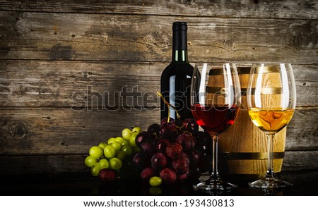 two glasses of wine with fresh grapes bottle and barrel in front of old grunge wooden planks