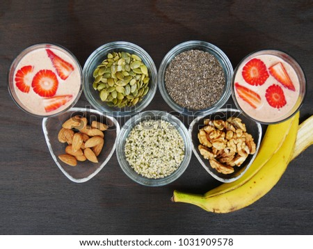 Two glasses of yogurt strawberry smoothie with  superfood seeds and nuts, chia, almond, walnut, hemp, pumpkin in glass bowl over dark wooden table
