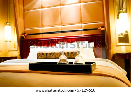 Two glasses on the double bed as romantic concept