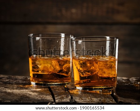 Two glasses whiskey with ice cubes on wooden background Foto stock ©