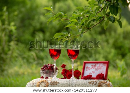 Two glasses with a red drink, a crystal vase with ripe cherries, a bouquet of red roses, a photo frame with a picture, stand on a table decorated with a beautiful tablecloth in a green garden in natur