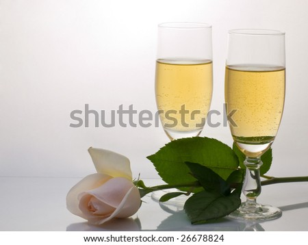 Two glasses  with by champagne and rose  on a grey  background - stock photo