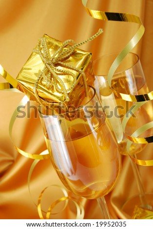 Two glasses with champagne and gift on gold background
