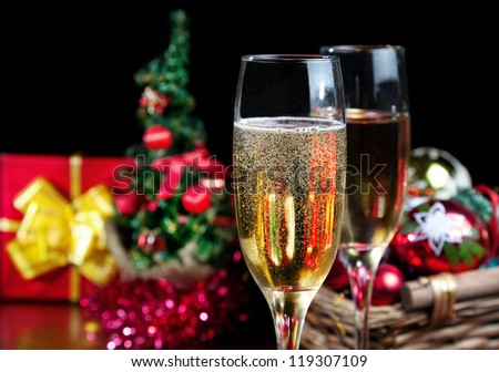 Two glasses with champagne and red box with yellow ribbon, Christmas tree and Christmas balls in the basket at black background. Free space for your text