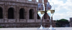 Two glasses with champagne are on the background of the Colosseum. Christmas concept. Christmas and New Year in Italy