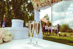 two glasses with champagne standing on the white table
