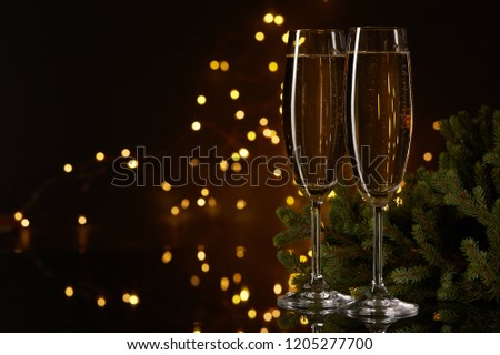 Two glasses with champange and fir tree on a dark background with LED lights garland. New year and Christmas. #1205277700