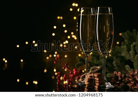 Two glasses with champange, fir tree branch and gingerbread cookies on a dark background with LED lights garland. New year and Christmas. #1204968175