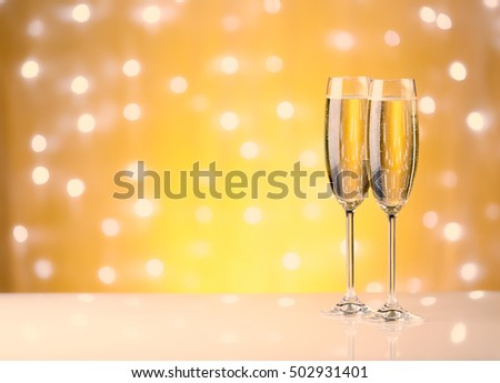 Two glasses with champange, gift boxes on a yellow background with lights of garland. #502931401