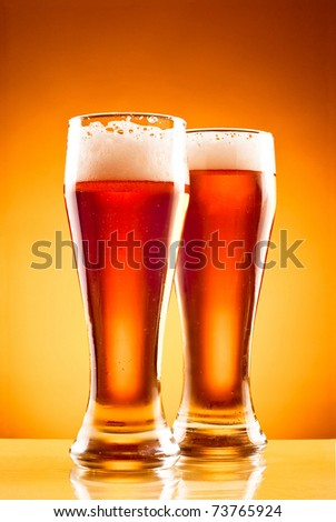 Two glasses with cold beer over yellow background