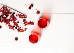 Two glasses with fruit juice made from red currants, cherries, black currants stand on a white wooden background, next to them are berries, top view, horizontal orientation, there is a copy space.
