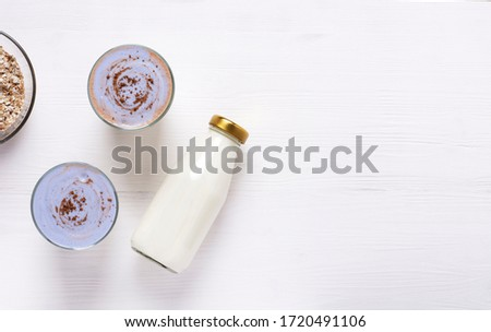 Two glasses with homemade kefir and granola with cinnamon are on a white wooden table, next to it is a bottle of kefir and a cup with granola. Top view, horizontal orientation, there is a copy space. Stok fotoğraf ©
