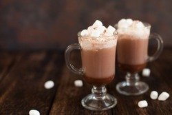 Two glasses with Hot chocolate garnished with whipped cream, marsmallow and cocoa powder. Winter and autumn time. Christmas drink