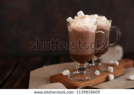 Two glasses with Hot chocolate garnished with whipped cream, marsmallow and cocoa powder. Winter and autumn time. Christmas drink #1139858609