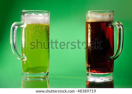 Two glasses with light and dark beer Artistic food still life over green background