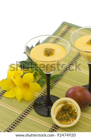 Two Glasses with passion fruit mousse and fresh, cut passion fruit, isolated on white