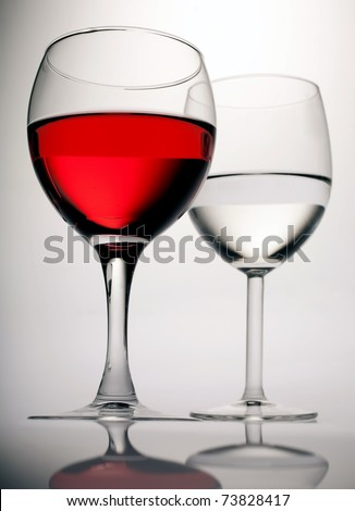 Two glasses with red wine  against a gradient from white to the black