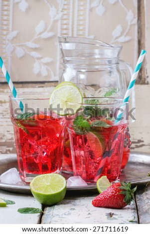Two glasses with retro cocktail tubes and glass jug of homemade strawberry lemonade, served with fresh strawberries, mint, lime and ice cubes over old white wooden table. See series