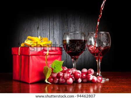 Two glasses with wine, grapes and red present with yellow bow. Wine pouring to the glass at textured wooden background