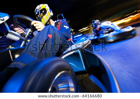 Two go-cart drivers battling in a competitive race on an indoor circuit - stock photo