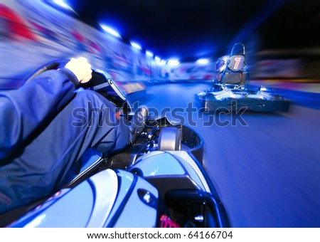 Two go-carts racing close to each other on an indoor race track - stock photo