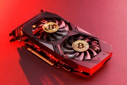 Two gold bitcoin on a  video Card with red backlight in the style of cyberpunk. Crypto currency. Bitcoin mining concept