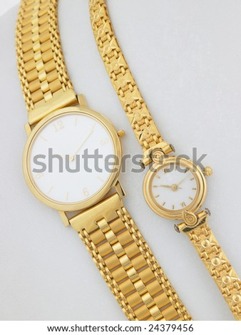 Two gold watches on white background