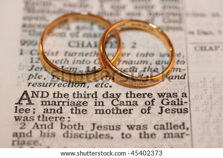 stock photo Two gold wedding bands on verse from Bible macro