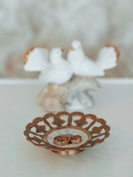 Two gold wedding bands symbolic of love and romance on a textured glitter plate with statuette in the form of doves