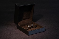 Two gold wedding rings in a brown box on a dark background.