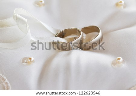 Two gold wedding rings on a pillow