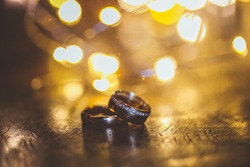 two golden alliance ring lit by Christmas yellow light and beautiful bukeh