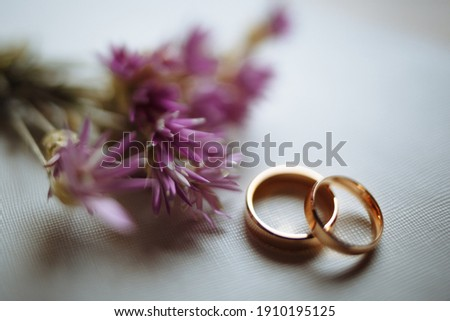 Two golden wedding rings and pink flowers on white background. Horizontally framed shot. Photo stock ©