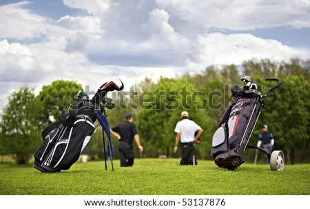 Two golf bags standing in front of a group of golf players putting on green.