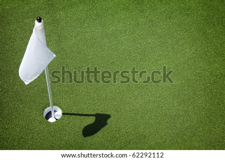 Two golf balls sit inside cup on golf course putting green with flag.