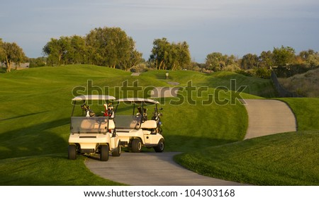 Two golf carts stand on the course path beside the ninth hole mature sport