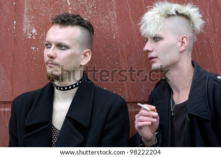 two goth boys against an aged red wall - stock photo