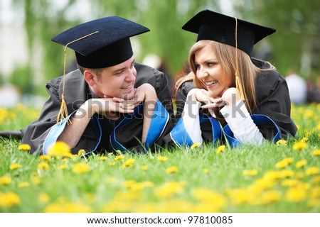 two graduate students guy and girl lying on spring grass smiling - stock photo