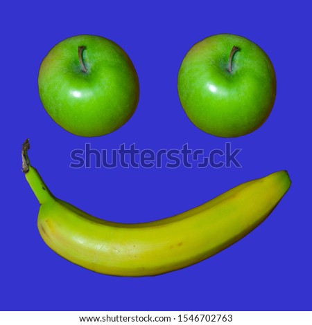 Two Granny Smith apples and a banana make a smiley face on a black background.