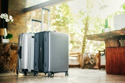 two gray large suitcases stand in the lobby of the hotel on the background of the waiting room and tropical greenery. The concept of vacation and travel.