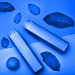 Two gray rectangle plastic cosmetic bottle on a blue background. Shampoo square bottle for gel or soap. Plastic container or package for brand merchandise isolated on blue background.