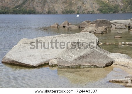 Two gray rocks on the beach with white sand