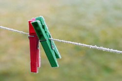 Two green and red clips or pegs for washing laundry covered with first frost on strip rope outdoor on green blurred grass background with copy space for text in early winter morning.